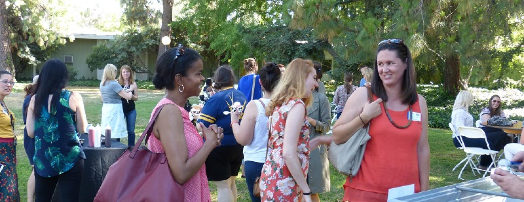 Advisors chat with smiles during outdoor event.