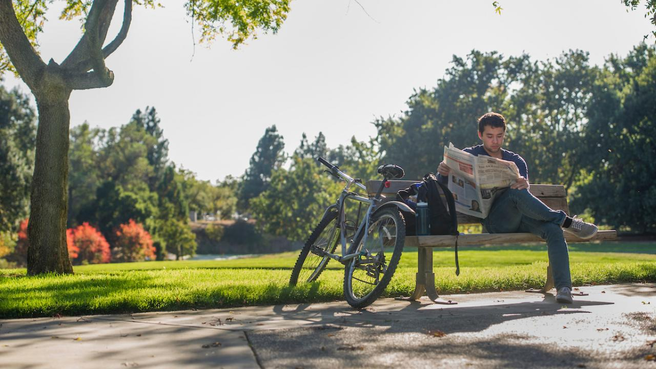 Student reading newspaper in arboretum.