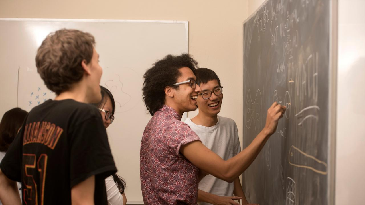 Students gather to problem solve at chalkboard.