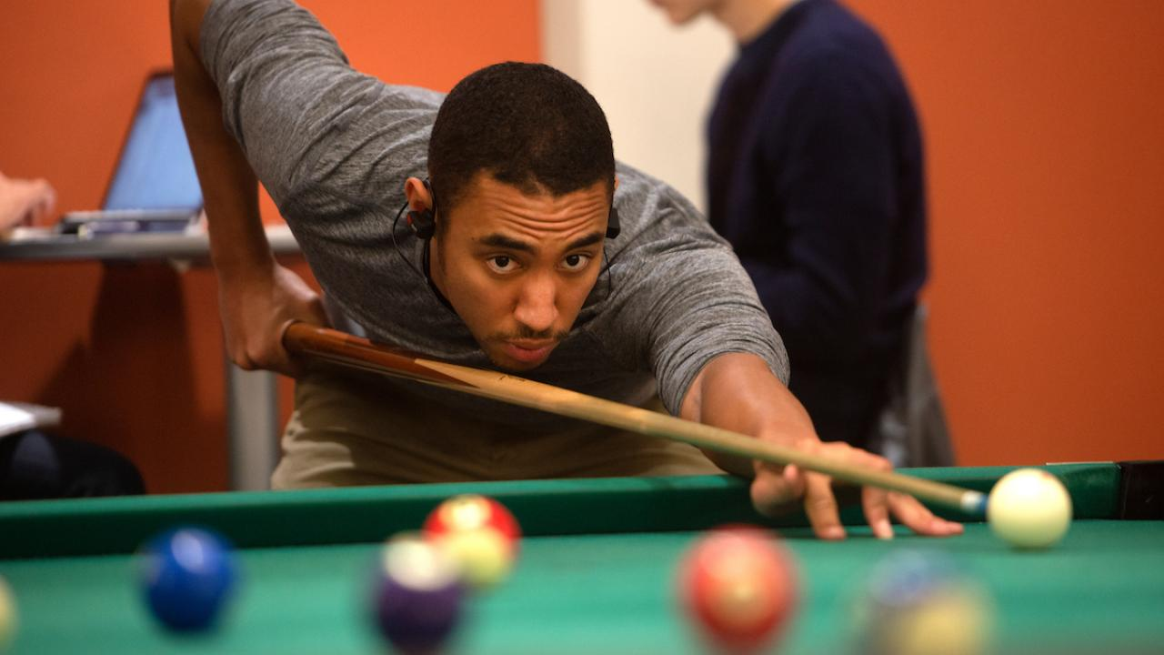 Student playing pool at the Billiards Hall.