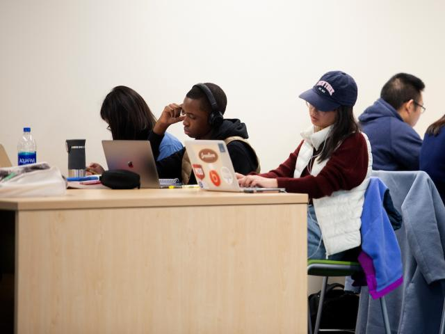 Students study in crowded library.
