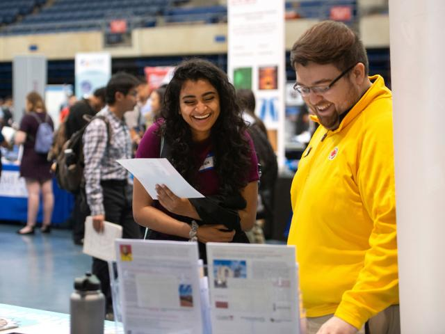 Student at career fair chats with a potential employer.