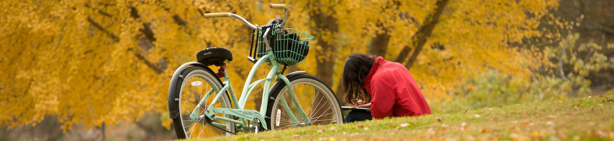 Student reading in leaf-covered grass, next to bike.